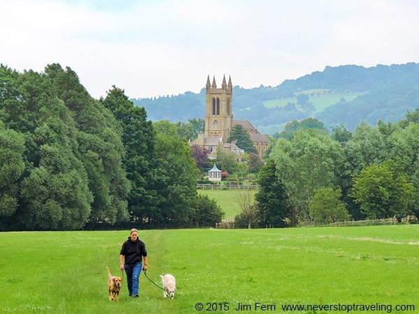 Foto Friday - a man with dogs walking across a field with a cathedral in teh background