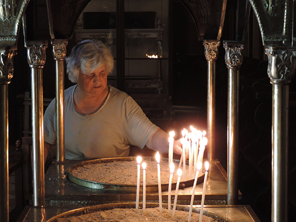 Foto Friday - a woman lighting a candle in a church