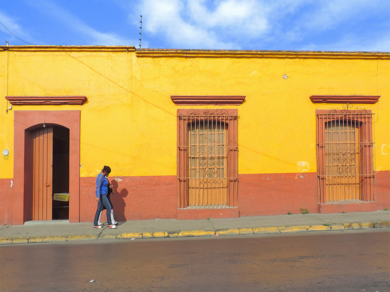 Foto Friday - a woman walking past brightly painted buildings-DSCN1942-600