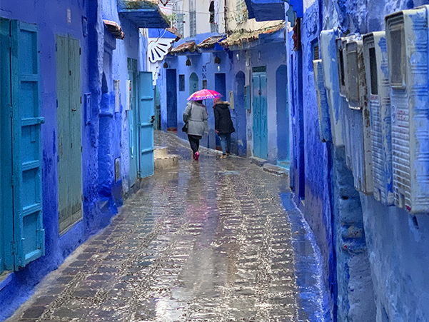 Foto Friday - a woman with a bright umbrella waling past blue-painted buildings