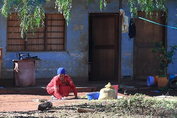 Foto Friday - a woman kneeling outside her home