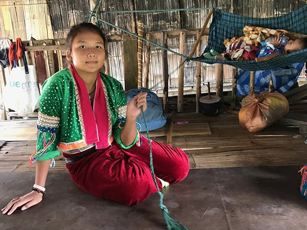 Foto Friday - a young girl inThai traditional dress rocking a baby