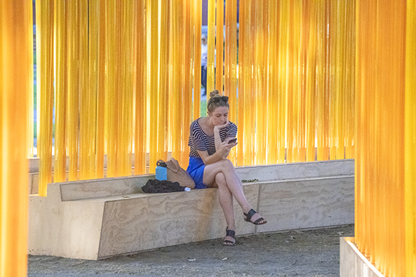 Foto Friday - a woman sitting in a bench by a yellow wall of streamers