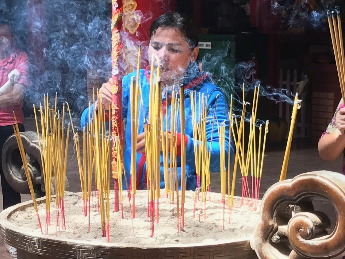 Foto Friday - a woman lighting incense sticks in a temple