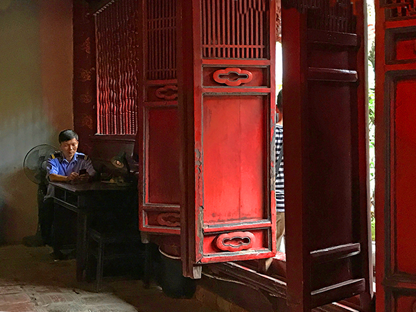 Foto Friday - a man sitting by bright-red shutters