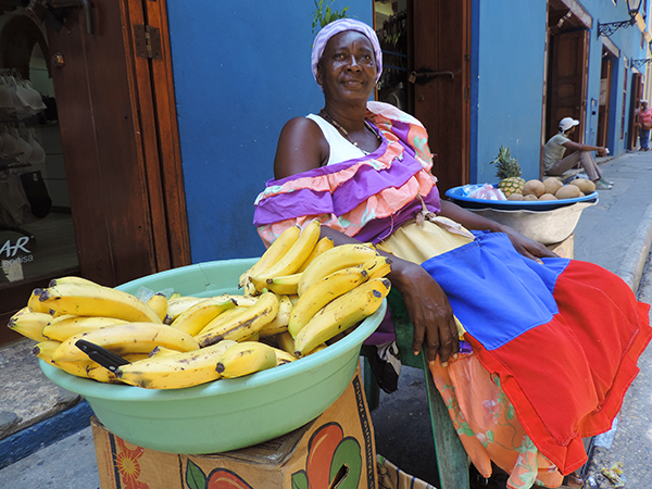 Foto Friday - a woman in a bright dress selling bananas on a street in Vartagena