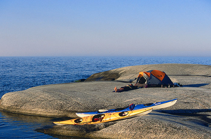 kayakers camped on a rocky island - top 10 places in sweden