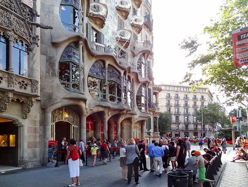 people visiting a modernistic Gaudi building, one of things to do in Barcelona