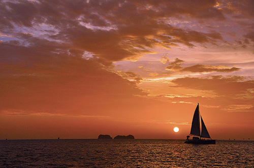 a boat on the water at sunset - things to do in costa rica