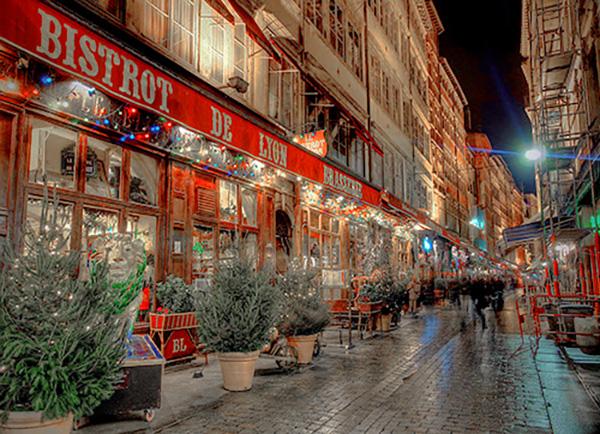 shops along an old city street at night