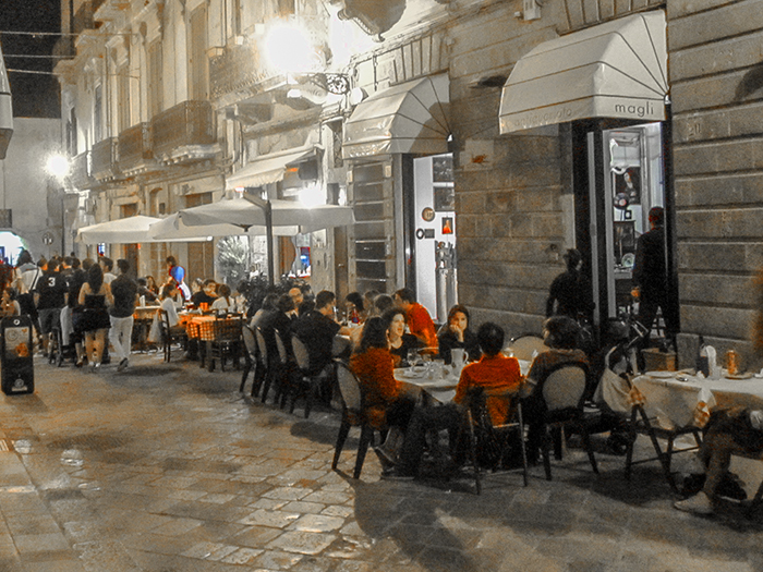 people having dinner in an outdoor cafe in Puglia, Italy