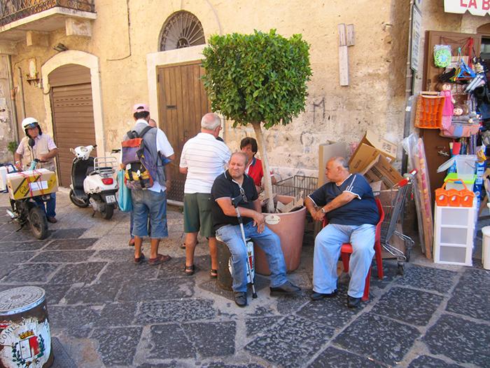 men sitting on a streetcorner in Puglia, Italy