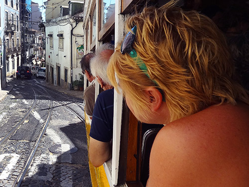 Passengers at the windows of Tram #28 in Lisbon
