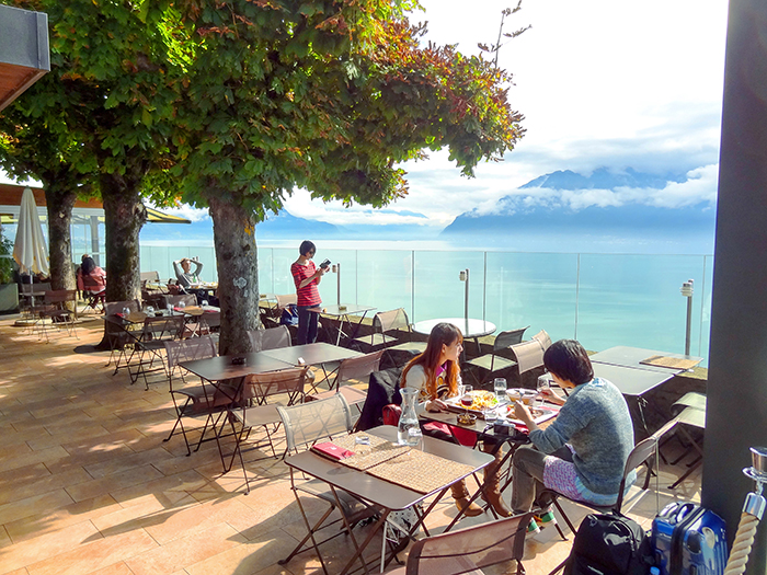 people in a café high above a lake in the Lavaux in Switzerland