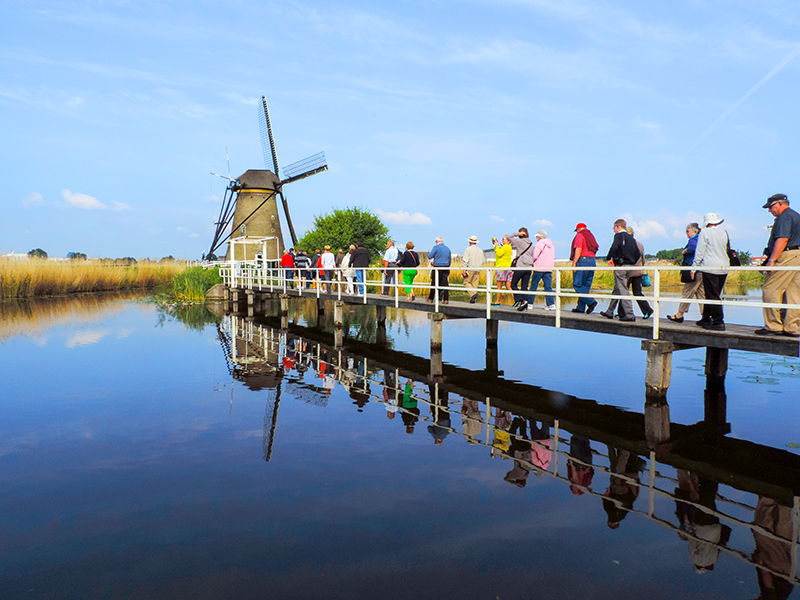 people walking towards a windmill