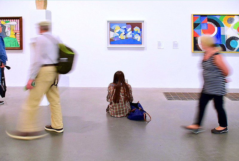 woman sitting on the floor of an art museum