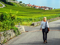 a woman walking through vineyards