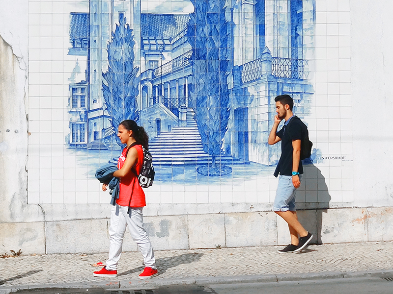 two pople seen walking along a tile wall in Coimbra, on a day trip from Lisbon