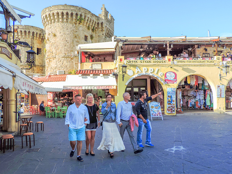 people walking by an old castle in Rhodes, Greece