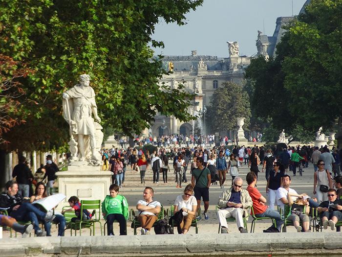 people sitting under a large statue in Paris seen during walks in Paris