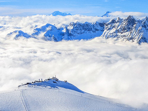 A view of teh Alps with clouds between the mountains