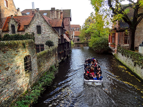 a canal boat with tourists passing old buildings