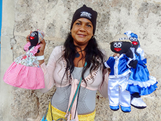 woman holding two puppets in Havana