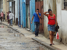 people walking past colorful buildings in Havana