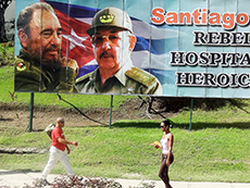 people walking by a poster of Fidel and Raul Castri in Havana