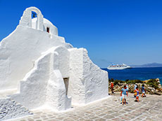 a small white church with people outside in Mykonos Town