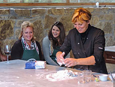 woman teaching two women to make pasta