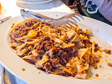 A freshly made dish of pasta and ragu on a table