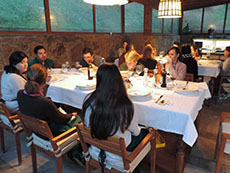 A cooking class seated at tables having the dinner they prepared