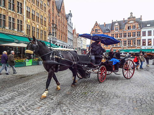 horse-drawn carriage on cobblestone plaza in Bruges