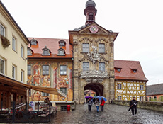 people walking past a building covered with colorful murals in a German river towns
