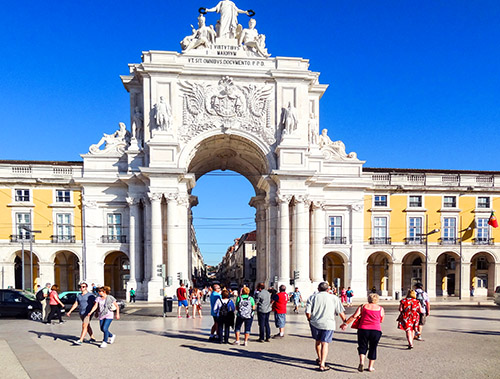 people walking towards a large ornate arch in Lisbon