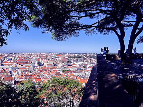 people looking over th city of Lisbon from a castle wall in Lisbon