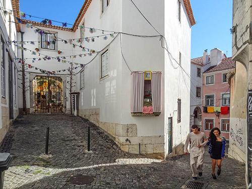 people walking on a hilly street in Lisbon