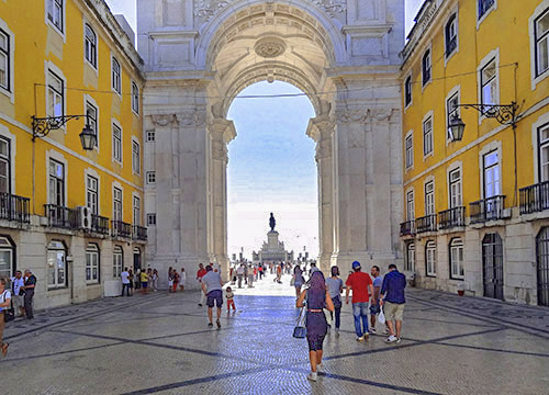 people walking towards a large arch in Lisbon