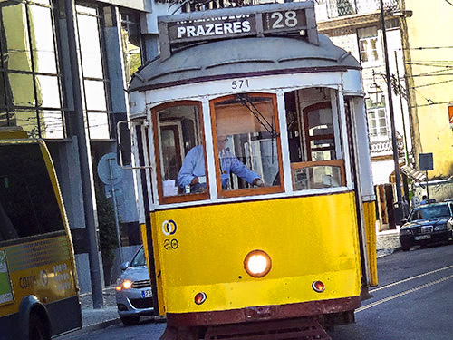 an old yellow trolley moving along the street in Lisbon