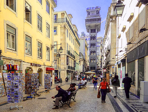 People sitting on a street with a tall tower elevator at the end in Lisbon