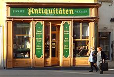 a couple walking past an antique shop