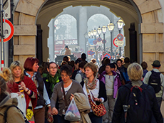 Crowd of people walking through an archway