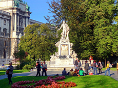 people sitting on the lawn in a park by a statue in Vienna
