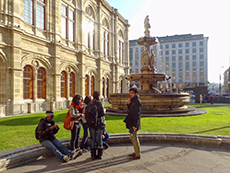 A group of people talking near a fountain by an ornate building
