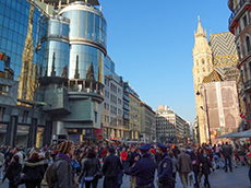 crowds of shopper passing modern and old buildings in Vienna