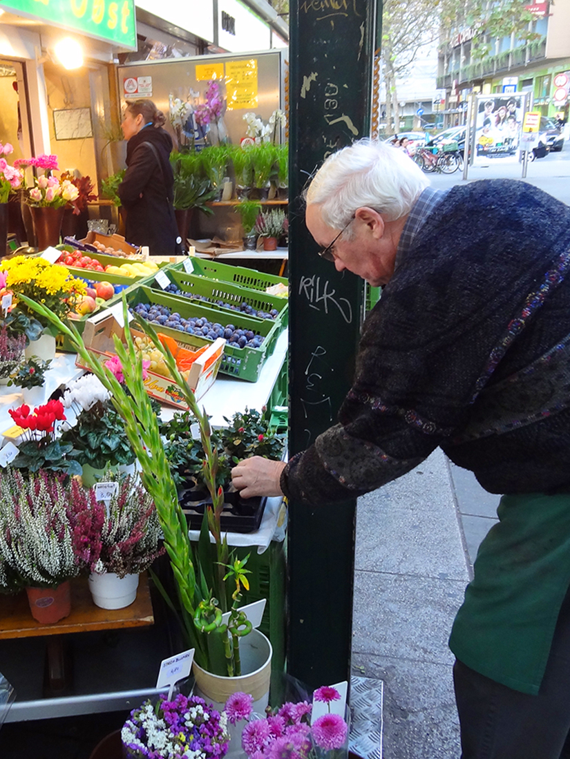 man looking at flowers in a market