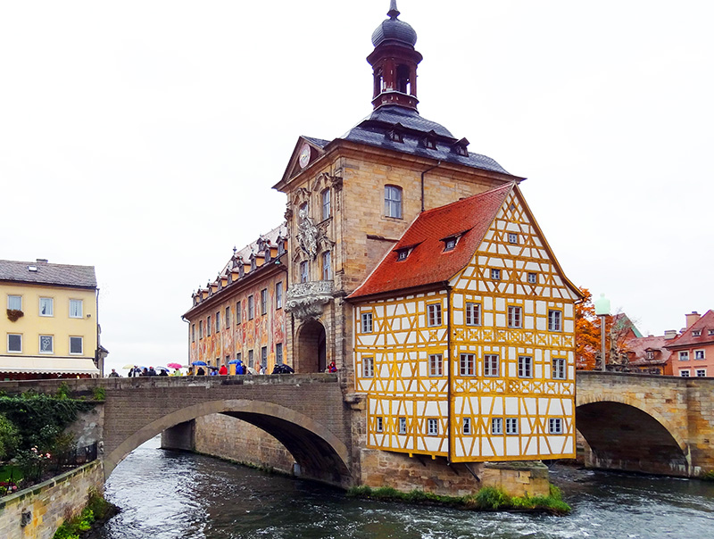 people on a bridge looking at old buildings on an island in a German river towns