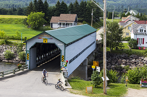 a covered bridge with people bicycling by it in Québec