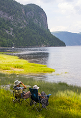people in chairs sitting along the shore of a fjord in Québec